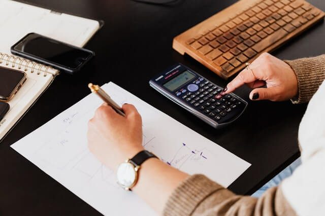 crop-woman-using-calculator-and-taking-notes-on-paper